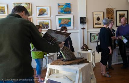 Art patrons viewing beaver art.